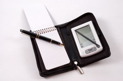 Paper Vs Technology. A PDA and a paper pad with pen both held in the same binder Royalty Free Stock Photos