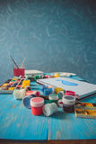Paper, watercolors, paint brush and some art stuff. On wooden table Royalty Free Stock Photography
