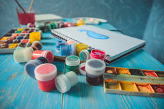 Paper, watercolors, paint brush and some art stuff. On wooden table Royalty Free Stock Photos