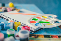 Paper, watercolors, paint brush and some art stuff. On wooden table Royalty Free Stock Images