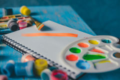 Paper, watercolors, paint brush and some art stuff. On wooden table Royalty Free Stock Image