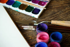 Paper, watercolors and paint brush on wooden background Stock Images