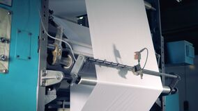Industrial paper roll is being processed by an industrial machine. 4K. stock video footage