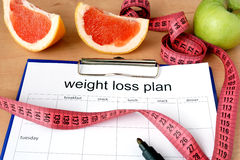 Paper with weight loss plan. And grapefruit Stock Images