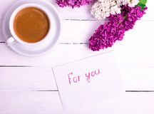 Paper white envelope with an inscription for you. And a white cup of coffee, near a bouquet of blossoming lilacs on a white wooden background, top view stock images