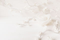 Paper white flowers and candle rose on white wooden background. Soft home decor Royalty Free Stock Image