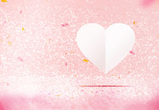 Paper white heart floating at pastel pink sparkling glitter room Royalty Free Stock Photo