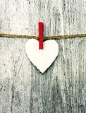 Paper white heart on a rope on grunge wooden background. Stock Photo