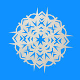 Paper white snowflake lie on blue background Royalty Free Stock Photos