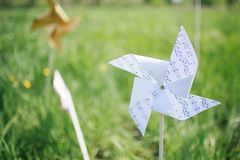 Paper windmill in green grass field Stock Image