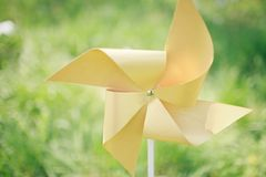 Paper windmill in green grass field Royalty Free Stock Photography
