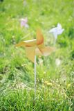 Paper windmill in green grass field Stock Images