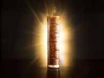 Paper wisdom. Old book  with glow behind   the magic of learning Royalty Free Stock Photography