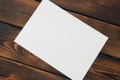 Paper on wooden background. With space for your text royalty free stock image