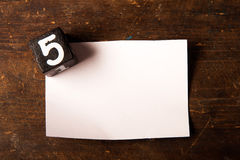 Paper and wooden cube with number on wooden table, 5 Stock Images