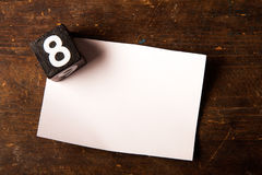 Paper and wooden cube with number on wooden table, 8 Royalty Free Stock Photo
