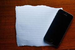 Paper on the wooden with mobile phone. Empty paper on the wooden with mobile phone Royalty Free Stock Image