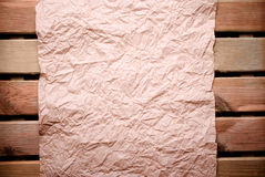 Paper on wooden wall. Old crumpled paper on wooden wall royalty free stock images