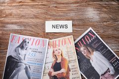 Paper with word NEWS and fashion magazines on wooden background royalty free stock images