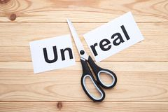 Paper with word Unreal. And scissors on wooden table royalty free stock photos