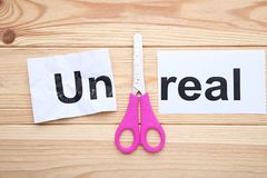 Paper with word Unreal. And scissors on wooden table royalty free stock images