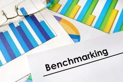 Paper with words Benchmarking. Paper with words Benchmarking and charts royalty free stock images