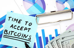 Paper with words time to accept bitcoins and graphs. Stock Photography