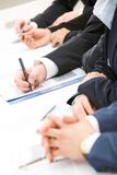 Paper work. Image of row of people hands over papers during briefing stock images
