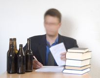 Paper work and beer. Confused man at a desk sorting out paper work Royalty Free Stock Images