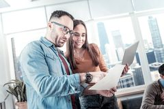 Bespectacled handsome man standing and overlooking documents. Paper work. Bespectacled handsome stylish men standing in the room with his colleague overlooking Royalty Free Stock Photo