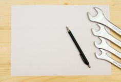 Paper with the working tool on wooden background Royalty Free Stock Images
