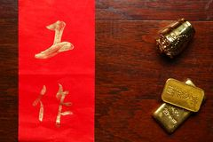 Paper wrote chinese text meaning of good wish beside plastic ancient chinese gold bar scene. Royalty Free Stock Photography