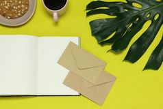 Paper notes, craft envelopes, green leaf, food on the yellow table stock photo