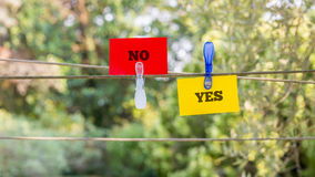 Paper with Yes and No Texts Clipped on a String Stock Photo