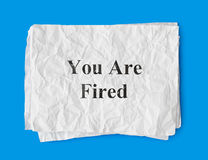 Paper You Are Fired. Isolated on blue background Stock Photo
