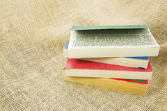 Paperback books piled burlap cloth background Stock Photos