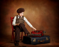 Paperboy with typewriter and suitcase. Boy sitting with typewriter and suitecase Stock Photo