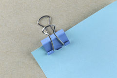 PaperClip action pin in blue paper note on Brown cardboard. Royalty Free Stock Photography