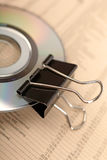 Paperclip and CD on financial newspaper. Close photo of paperclip attached to disk laying on financial newspaper Royalty Free Stock Photo