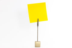 Paperclip holds yellow sticky note Stock Images