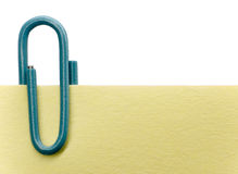 Paperclip on a note. Blue paperclip on a yellow note with white background Royalty Free Stock Photography