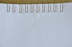 Paperclip på vitbok Royaltyfri Bild