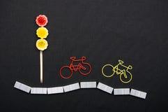 Paperclippen in een vorm van fiets dichtbij het licht van snoepjes Royalty-vrije Stock Foto's