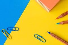 Paperclips, blyertspennor och ett minneslistakvarter som isoleras mot en blått och Royaltyfri Foto