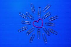 Paperclips coloridos en fondo azul Imagen de archivo