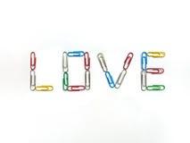 Paperclips del color a amar en el fondo blanco fotos de archivo libres de regalías