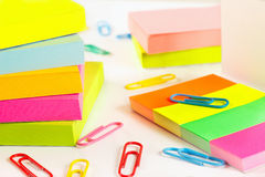 Paperclips and multicolored stickers on white desktop closeup Royalty Free Stock Photos