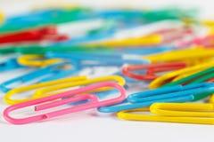 Paperclips multicolores brillantes de la oficina en el cierre blanco de la mesa para arriba Imagen de archivo libre de regalías