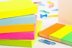 Paperclips, pasadores y etiquetas engomadas multicoloras en el primer de escritorio blanco Foto de archivo