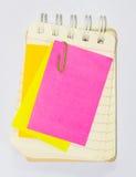 Paperclips, post-it y cuaderno coloridos en el fondo blanco i Fotos de archivo